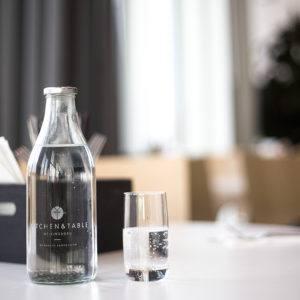Karaff med vatten och vattenglas på bord